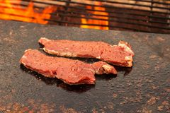 Grilling beef steak on a granite plate. Preparation of meat on an outdoor fire. Summer barbecue. Grilling beef steak on a granite plate. Preparation of meat on royalty free stock photo