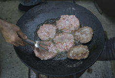Grilling beefburgers on hot oil Stock Images