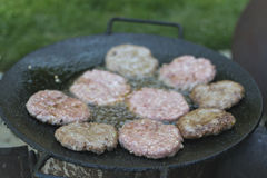 Grilling beefburgers on hot oil.  Royalty Free Stock Photography