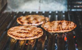 Grilling burgers on barbecue BBQ grill on hot charcoal. Homemade burger patties are being roasted on ECO grill bars for healthy eating and cooking Royalty Free Stock Image