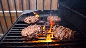 Grilling burgers on a barbecue stock images