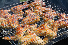 Grilling chicken on a barbecue Stock Images