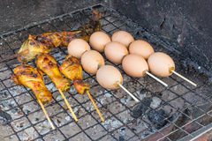 Grilling chicken and egg. Leg on the stove Royalty Free Stock Photo