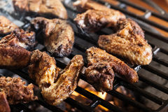 Grilling chicken wings on barbecue grill Stock Images