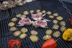 Grilling delicious poultry quails on barbecue. Pepper, quail and potato prepared on the grill on sunny day. Culinary concept with delicious food Stock Photo