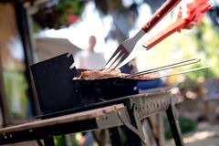 Grilling food on barbecue grill, hands preparing skewers Royalty Free Stock Image