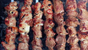 Grilling food on mangal. Rotate skewers with roasted meat. Prepared food. Macro stock footage