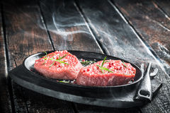 Grilling fresh piece of red meat with herbs Royalty Free Stock Photos