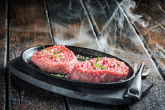 Grilling fresh piece of red meat with herbs Royalty Free Stock Photography