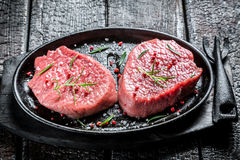 Grilling fresh piece of red meat with rosemary Stock Image