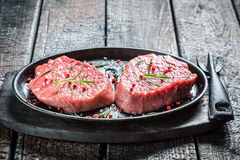 Grilling fresh piece of red meat with rosemary Royalty Free Stock Images