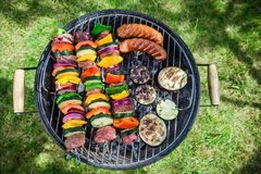 Grilling fresh vegetables and meat with herbs in garden Stock Image