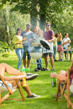 Grilling is fun. Group of friends having fun during grilling together Stock Images