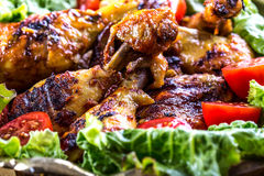 Grilling. Grilled chicken. Grilled chicken legs. Grilled chicken legs, lettuce and cherry tomatoes. Traditional cuisine. Mediterra Royalty Free Stock Photo