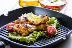 Grilling. Grilled chicken. Grilled chicken legs. Grilled chicken legs, lettuce and cherry tomatoes. Traditional cuisine. Mediterra Stock Image