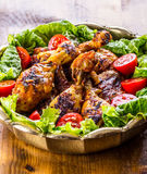 Grilling. Grilled chicken. Grilled chicken legs. Grilled chicken legs, lettuce and cherry tomatoes. Traditional cuisine. Mediterra Royalty Free Stock Images