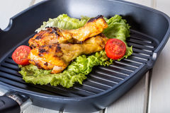 Grilling. Grilled chicken. Grilled chicken legs. Grilled chicken legs, lettuce and cherry tomatoes. Traditional cuisine. Mediterra Royalty Free Stock Photography