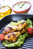 Grilling. Grilled chicken. Grilled chicken legs. Grilled chicken legs, lettuce and cherry tomatoes. Traditional cuisine. Mediterra Stock Photography