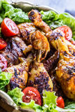 Grilling. Grilled chicken. Grilled chicken legs. Grilled chicken legs, lettuce and cherry tomatoes. Traditional cuisine. Mediterra Stock Photo