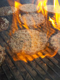 Grilling hamburger. Hamburger on the grill with flames Royalty Free Stock Photography
