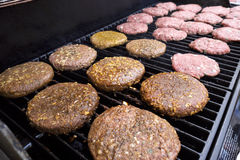 Grilling hamburgers. Hamburger patties grilling outdoors on a gas barbeque grill Royalty Free Stock Photo