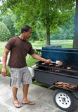 Grilling Hamburgers. Man flipping burgers on the grill Stock Image