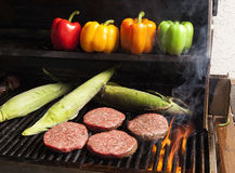 Grilling Hamburgers and Corn. Hamburgers being being grilled along with corn on the cob with bell peppers in the background Royalty Free Stock Images