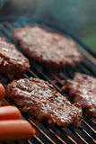 Grilling hamburgers and hot dogs. Hot dogs and hamburgers on a grill with smoke Royalty Free Stock Photography