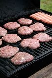 Grilling Hamburgers and Hotdogs. Some hambugers and hotdogs are put on the grill for a cookout Royalty Free Stock Photography