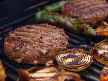 Grilling homemade hamburgers on a grill BBQ. Grilling homemade hamburgers on a BBQ grill in a garden party Stock Photos