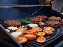 Grilling homemade hamburgers on a grill Stock Images