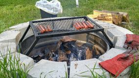 Grilling hotdogs over a fire-pit stock images