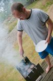 Grilling man. Man cooking burgers outside on a terrace royalty free stock photos