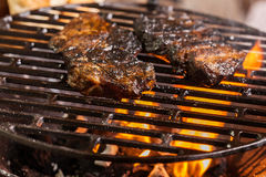 Grilling marinated pork meat on a charcoal grill Royalty Free Stock Images