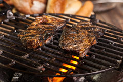 Grilling marinated pork meat on a charcoal grill Royalty Free Stock Photography
