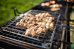 Grilling marinated shashlik on a grill. Shashlik is a form of Shish kebab popular in Eastern, Central Europe and other places. Shashlyk meaning skewered meat Stock Photos