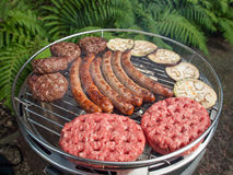 Grilling meat and aubergines on a barbecue. Sausages beefburgers  and sliced aubergines cooking on a charcoal grill in a garden Royalty Free Stock Photos