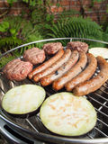Grilling meat and aubergines on a charcoal grill. Sausages and beefburgers cooking on a barbecue  in a garden Stock Photos