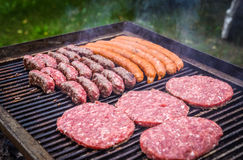 Grilling Meat on barbecue grill with coal. Royalty Free Stock Images