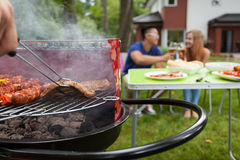 Grilling meat on a barbecue Stock Image