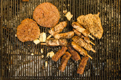 Grilling the meat and cheese on metal grill - bird's eye view Royalty Free Stock Images