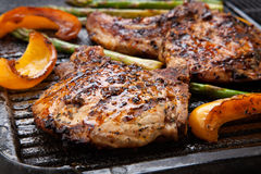 Grilling Pork Chops. Juicy pork chops are grilled on griddle with asparagus and bell pepper. Backyard grilling for summer picnic Royalty Free Stock Photography
