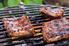 Grilling pork spareribs on barbecue grill Royalty Free Stock Images
