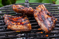 Grilling pork spareribs on barbecue grill Stock Photos