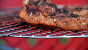 Grilling pork steak on the flaming grill stock video footage