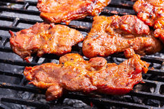 Grilling pork steaks on barbecue grill Stock Photo