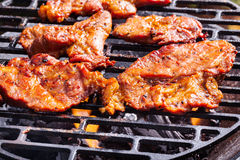 Grilling pork steaks on barbecue grill Royalty Free Stock Photos