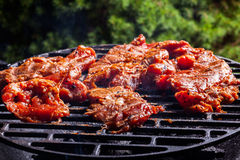 Grilling pork steaks on barbecue grill Royalty Free Stock Photo
