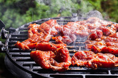 Grilling pork steaks on barbecue grill Royalty Free Stock Photography