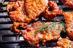 Grilling pork steaks on barbecue grill Royalty Free Stock Images